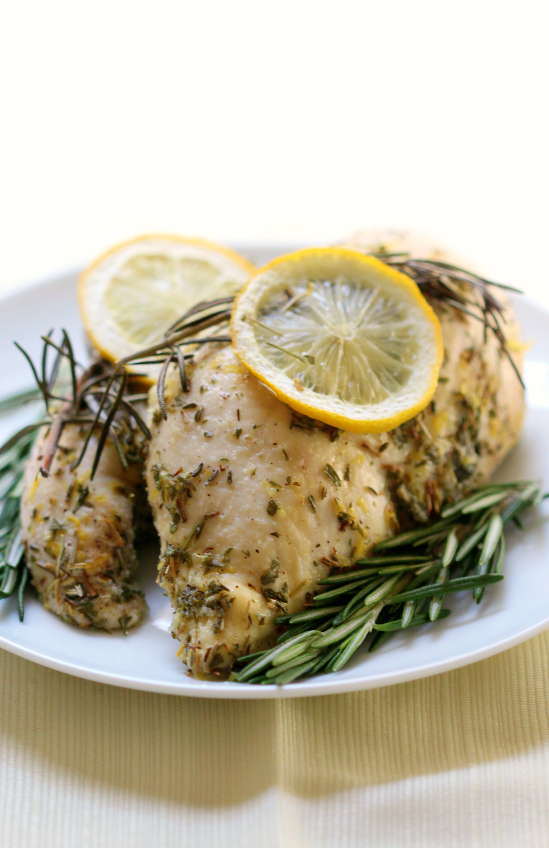 Perfectly baked and zesty lemon rosemary chicken breasts for an easy weeknight dinner recipe. A quick gluten-free and paleo option to flavor up bland chicken with just two simple ingredients! Paired with savory paprika oregano roasted acorn squash and you have a complete family meal!