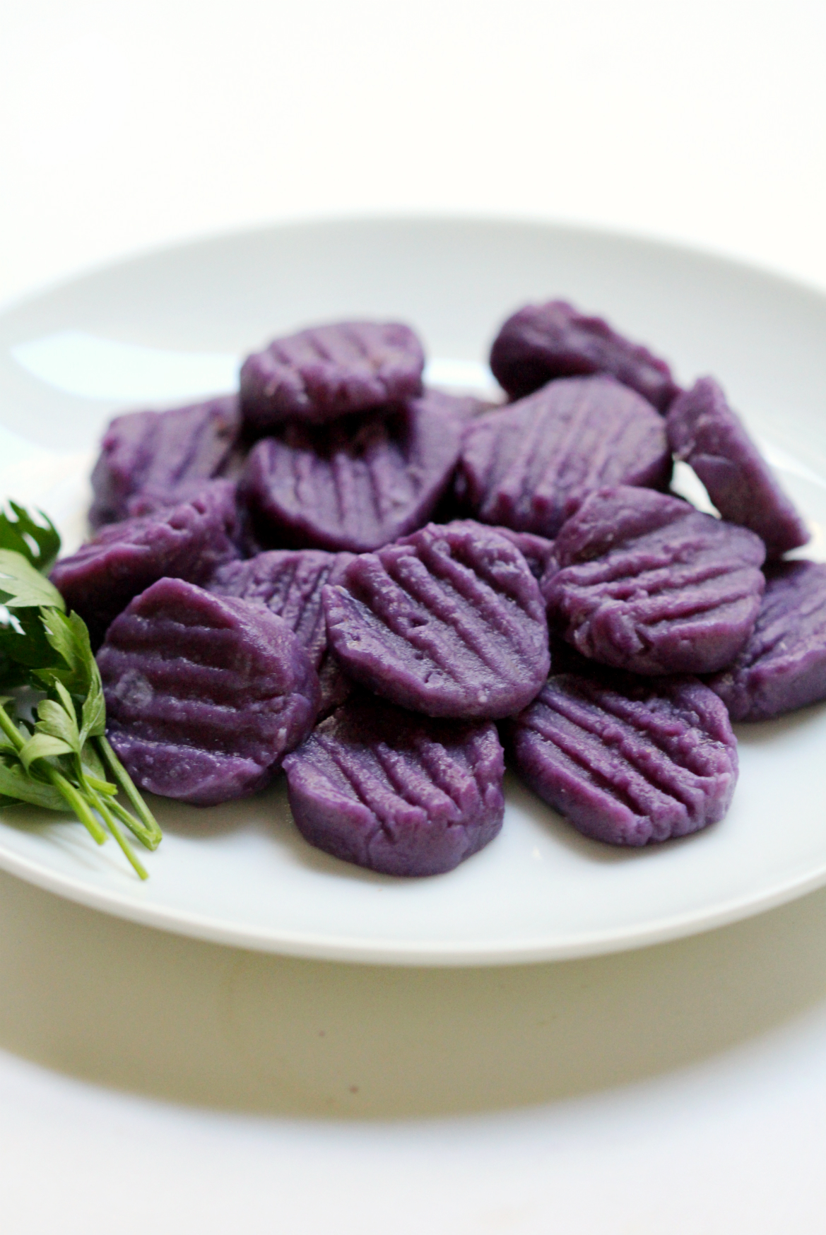 Purple Sweet Potato Gnocchi + Tahini Parsley Sauce | Strength and Sunshine @RebeccaGF666 You won't believe how easy homemade gnocchi can be! With the stunning color of purple sweet potatoes and the taste of creamy tahini with parsley and garlic, this gluten-free, vegan, nut-free, and paleo recipe will blow everyone's mind! An elegant dinner or date night dish!