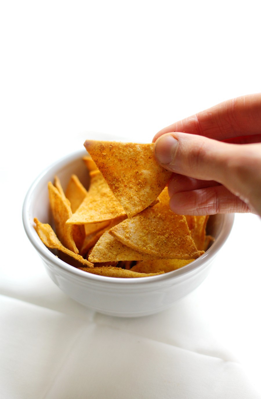 hand-grab-vegan-dorito-from-white-bowl