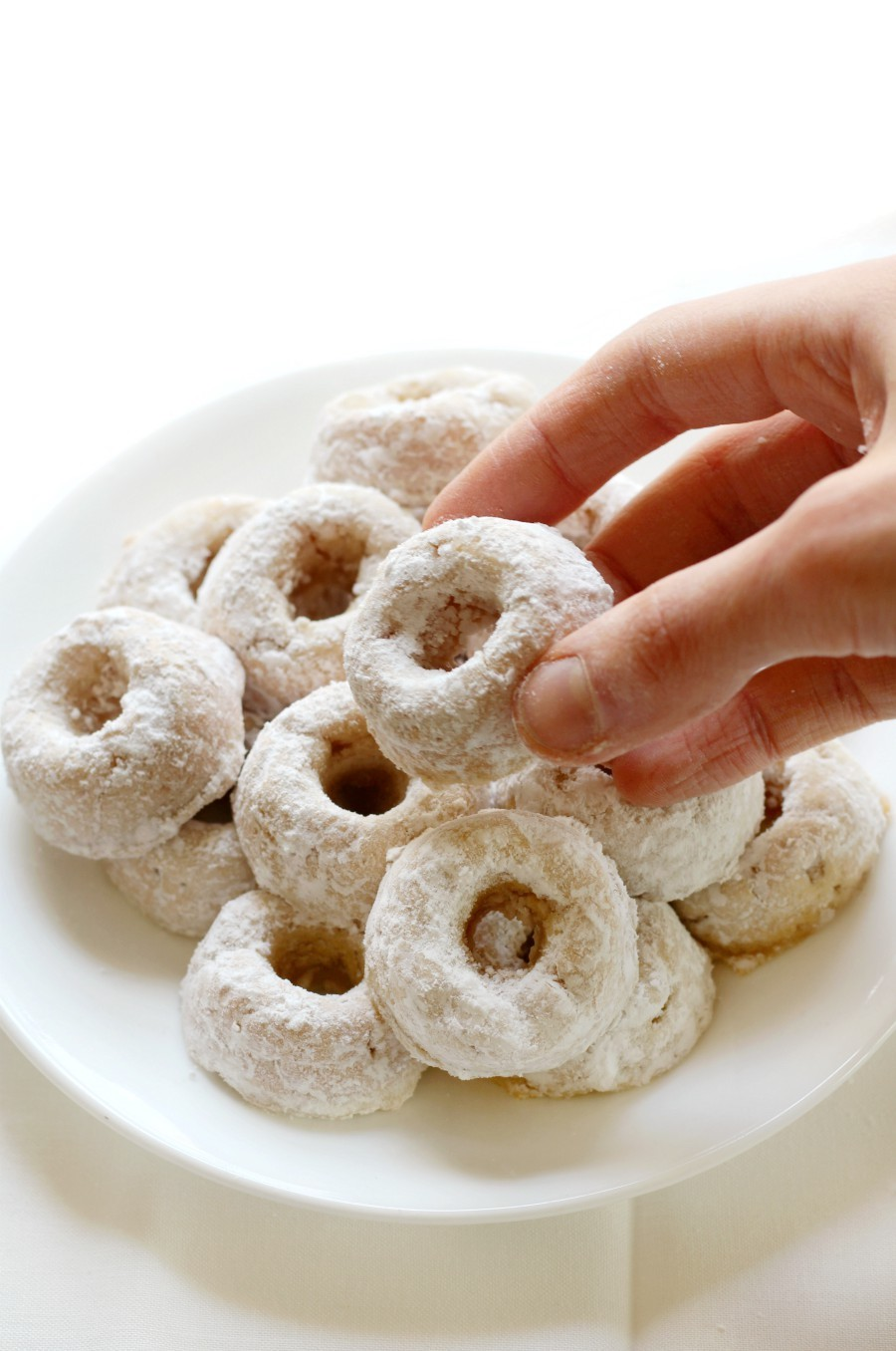 hand-grab-mini-powdered-doughnut-from-white-plate-pile