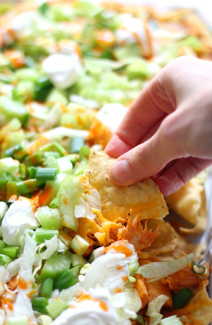 hand-scooping-vegan-buffalo-chicken-nachos
