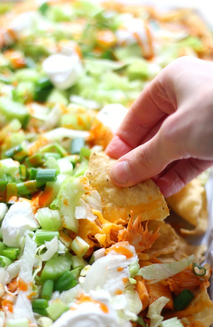 hand-scooping-vegan-buffalo-chicken-nachos