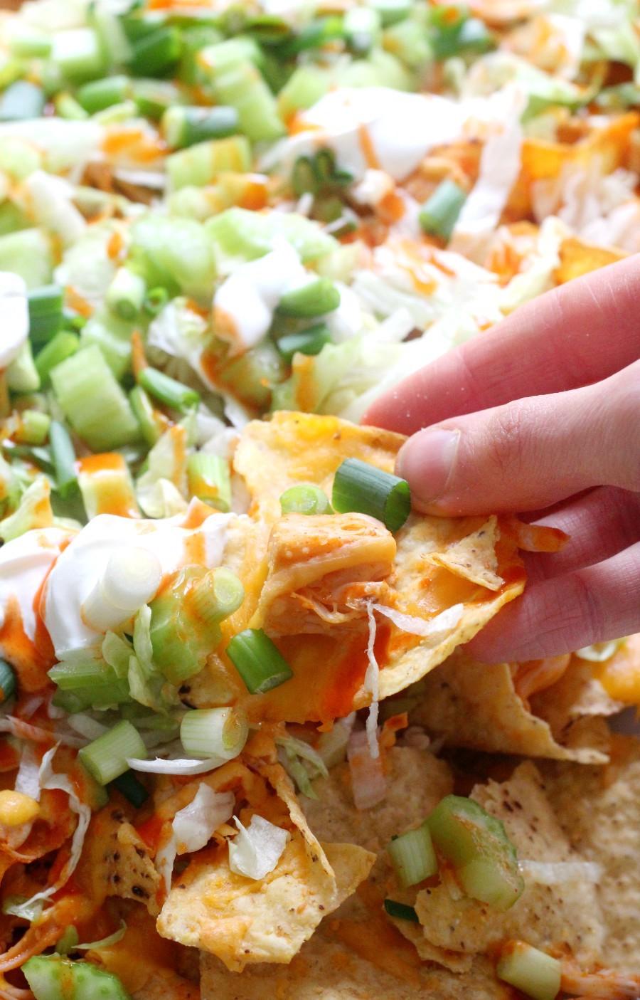 close-up-hand-grabbing-vegan-buffalo-chicken-nachos
