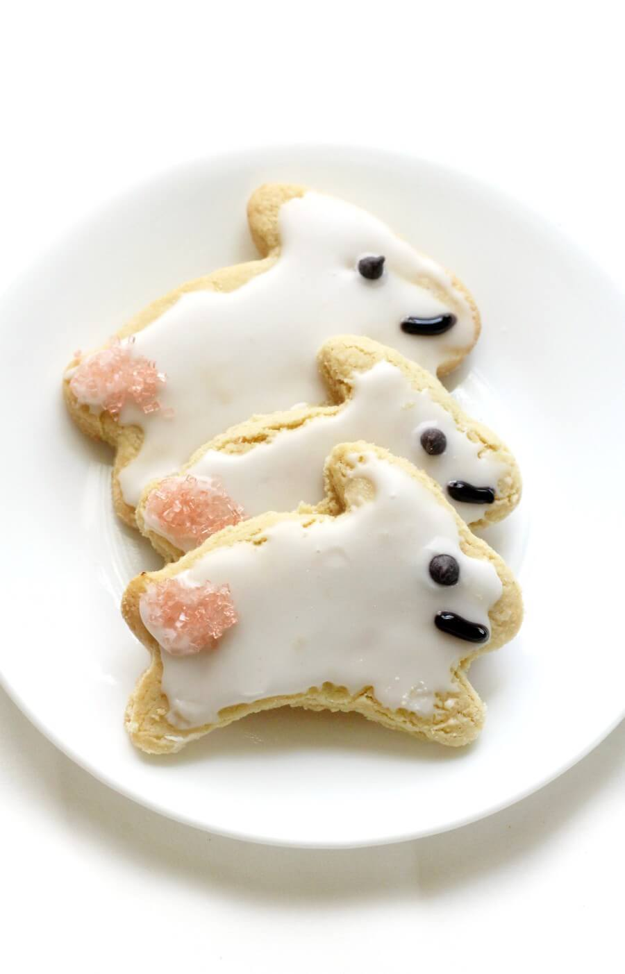 three decorated gluten-free easter bunny cut-out sugar cookies on a white plate