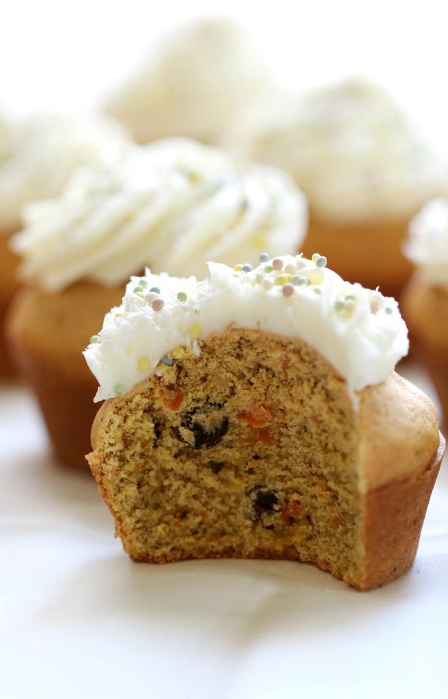 half eaten gluten-free carrot cake cupcake with vegan cream cheese frosting