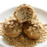 three banana sunflower mini muffins on a plate with sunflower seeds