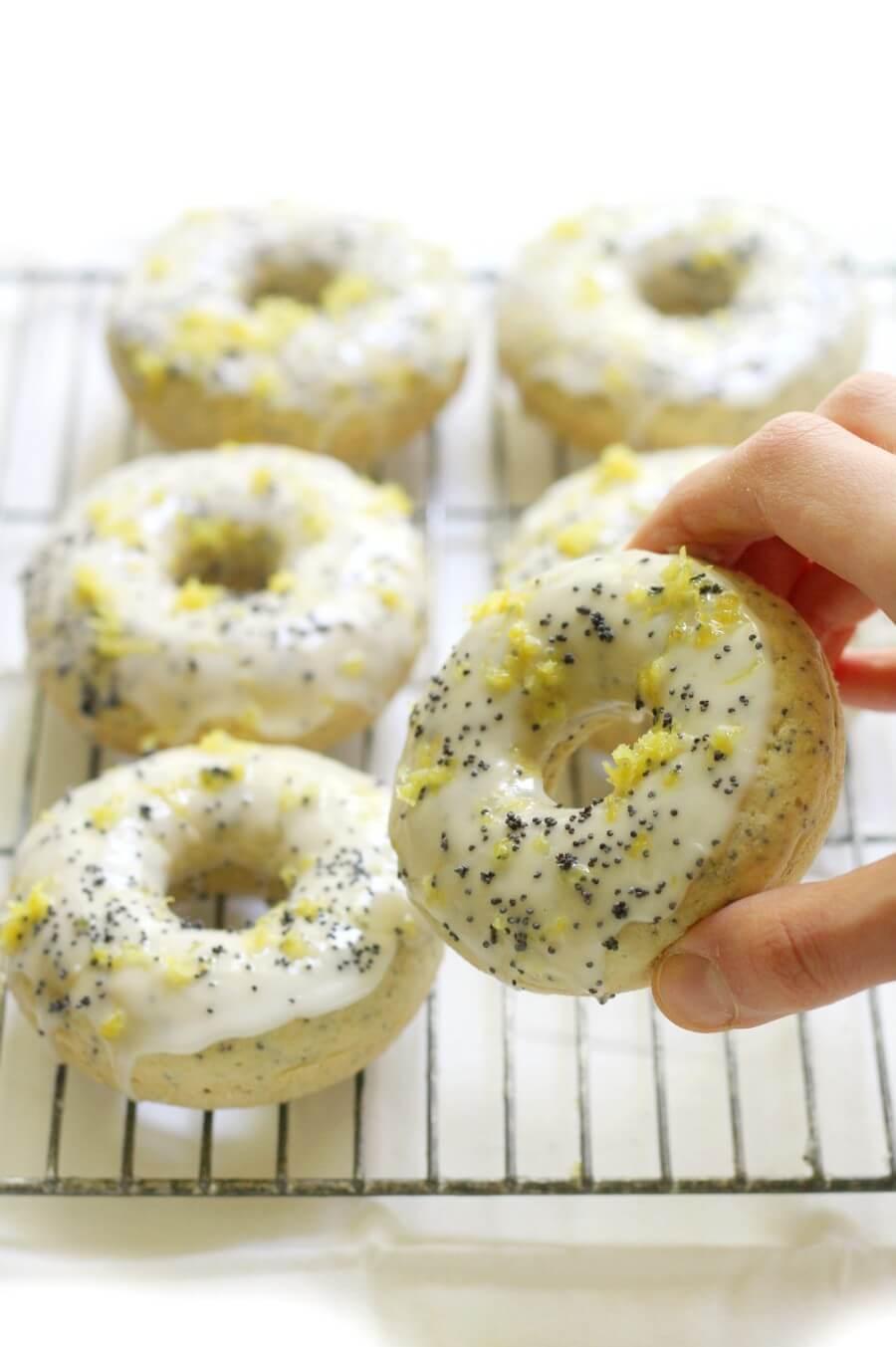hand grabbing a glazed gluten-free lemon poppy seed doughnuts
