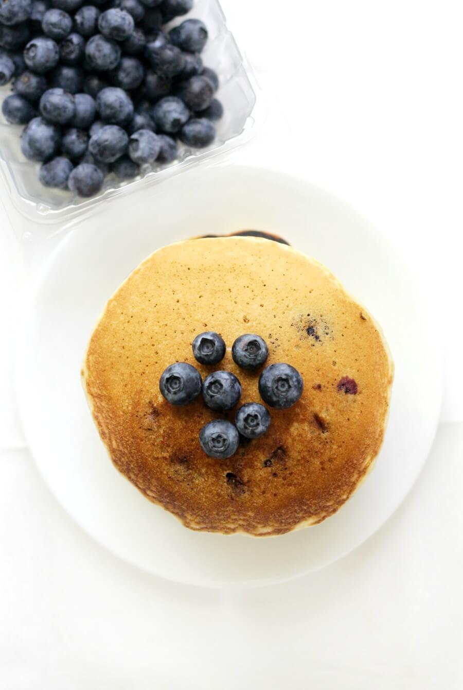 overhead view of gluten-free blueberry pancakes on white plate with carton of fresh blueberries