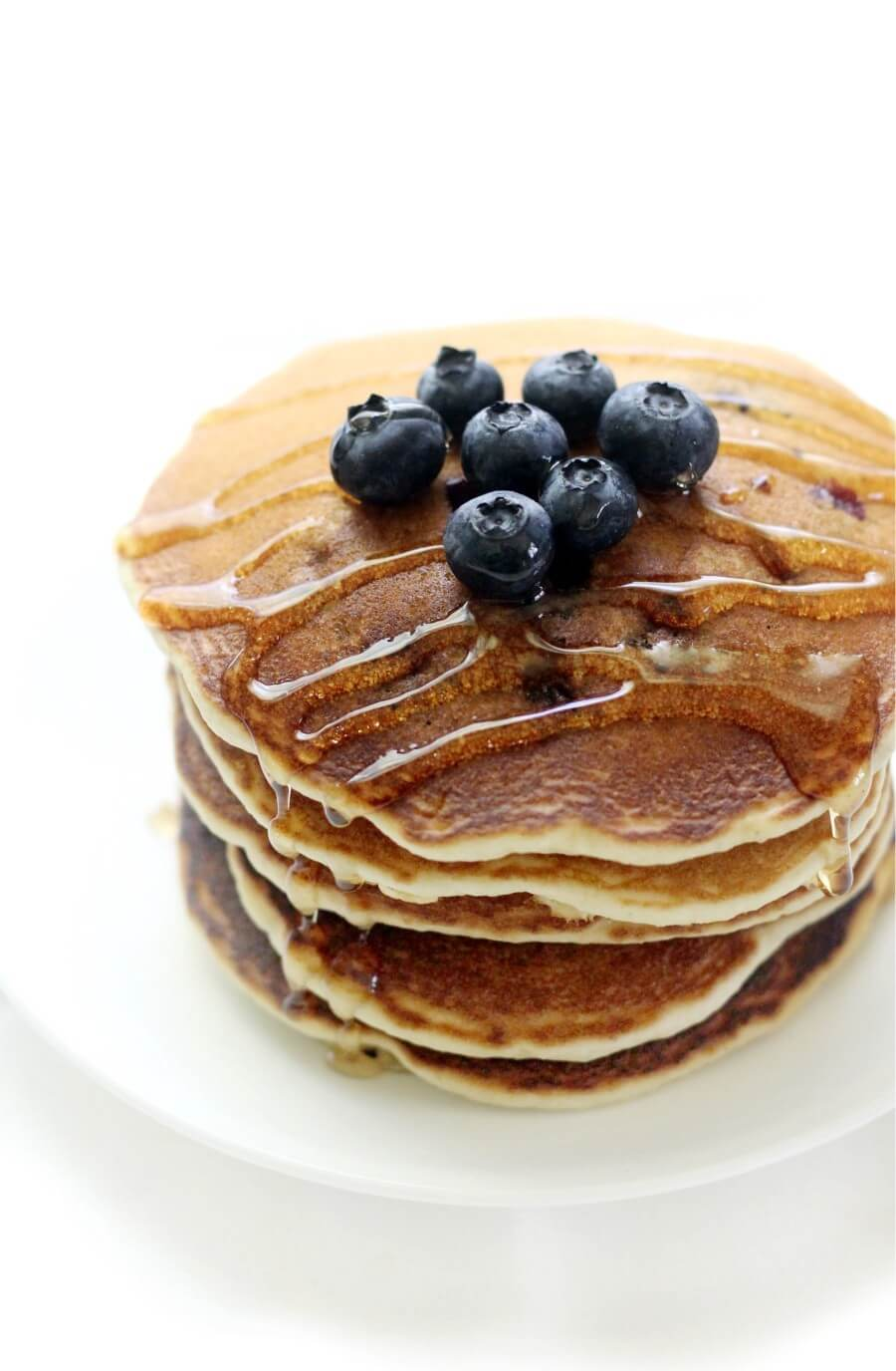close-up of syrup drizzled gluten-free blueberry pancakes on white plate