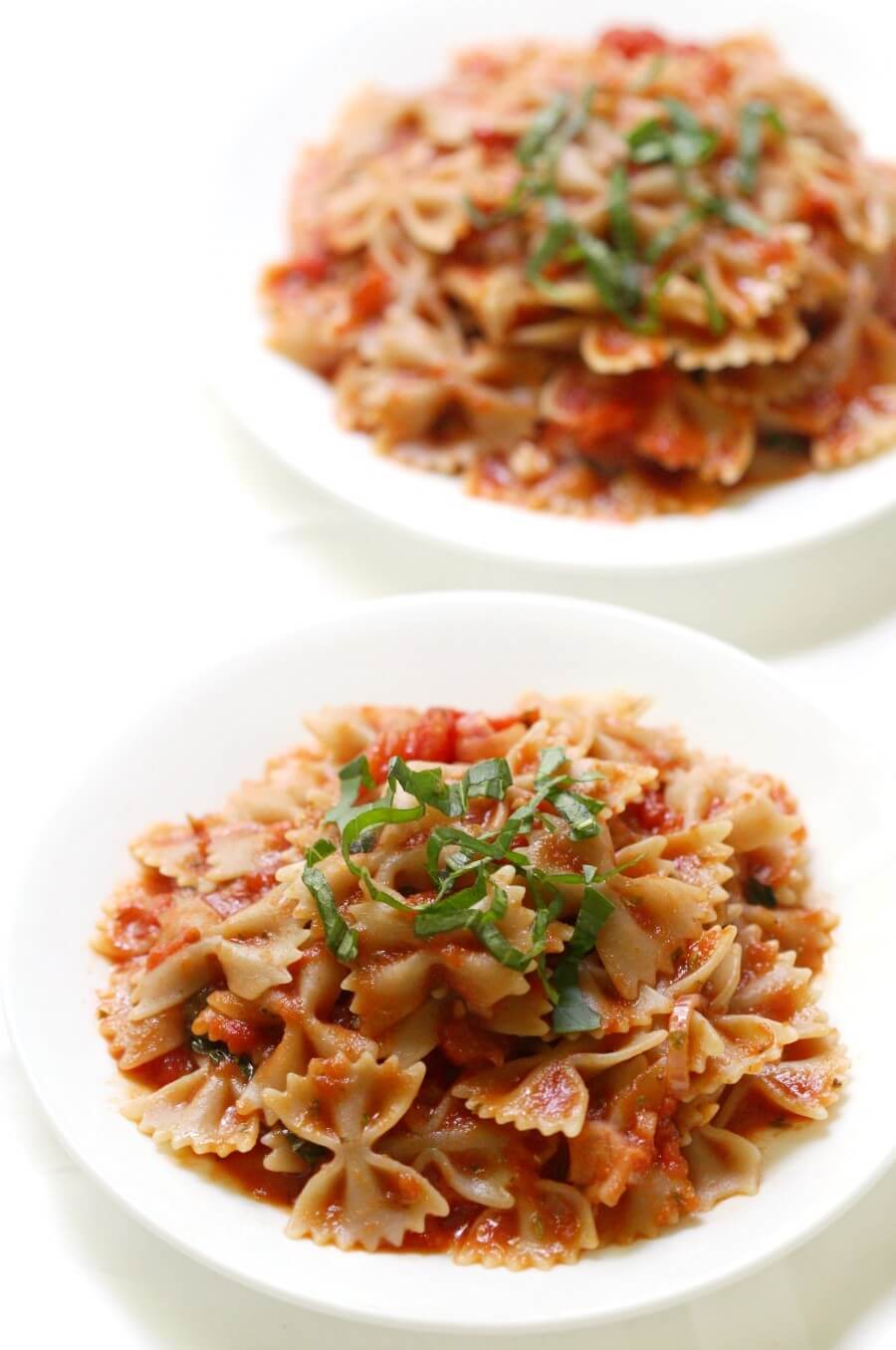two white plates of gluten-free farfalle pasta with homemade sauce