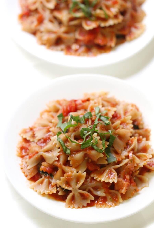 white plates of gluten-free farfalle bow-tie pasta with tomato basil sauce