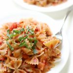 forkful of gluten-free farfalle pasta with homemade tomato basil sauce