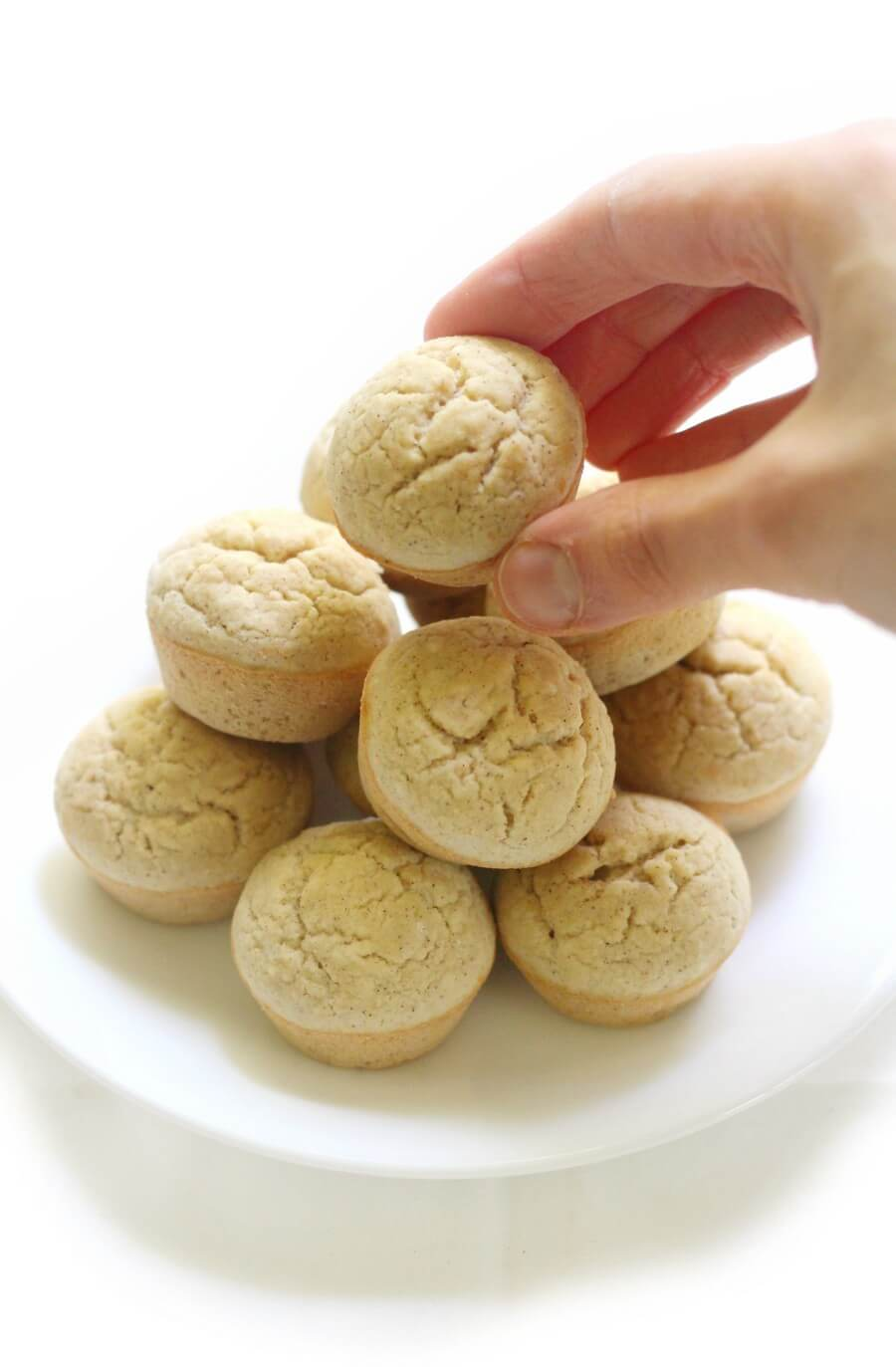 hand grabbing a gluten-free applesauce muffin from white plate