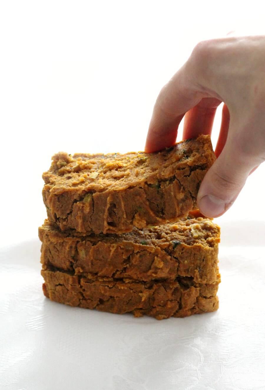hand grabbing a slice of gluten-free pumpkin zucchini bread