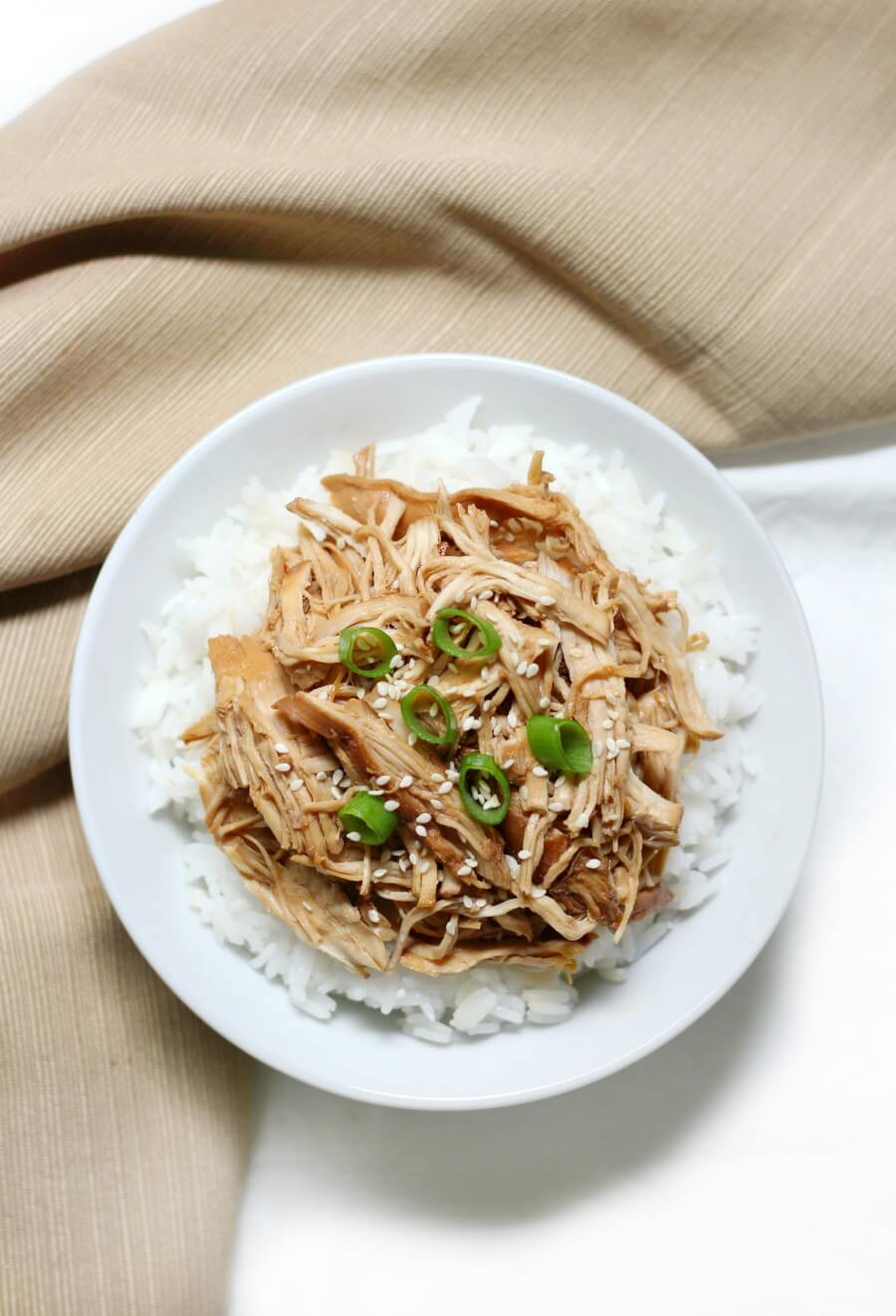 overhead view of pulled slow cooker teriyaki chicken in a bowl with rice