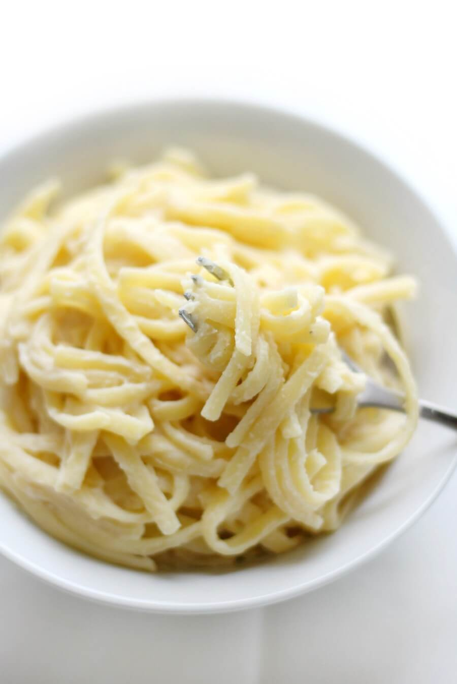 fork twirled with gluten-free fettuccine alfredo in white bowl