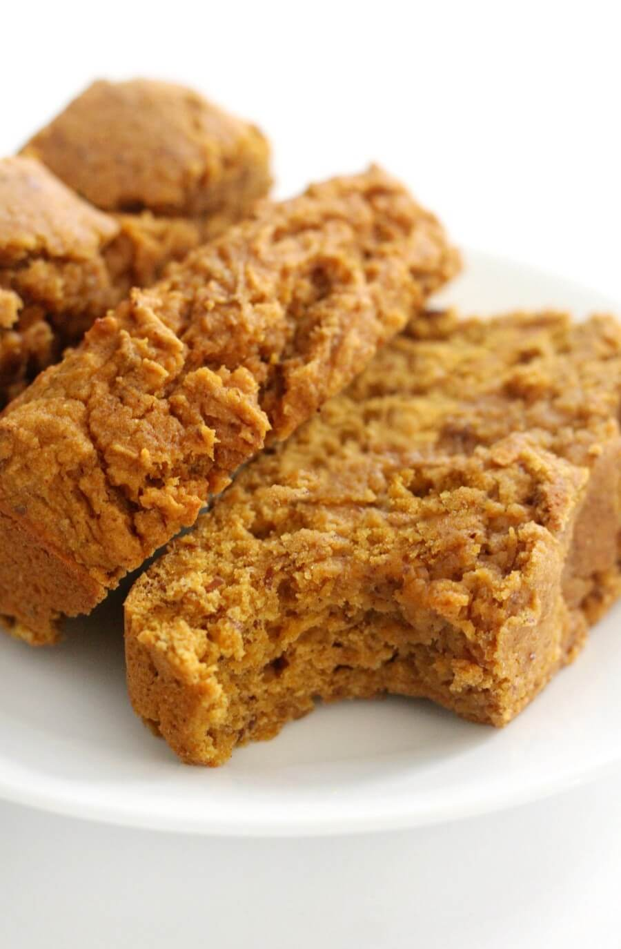 half-eaten slice of gluten-free pumpkin bread on white plate