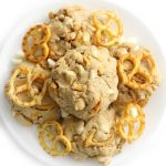 overhead view of loaded vegan white chocolate chip pretzel cookies on a plate