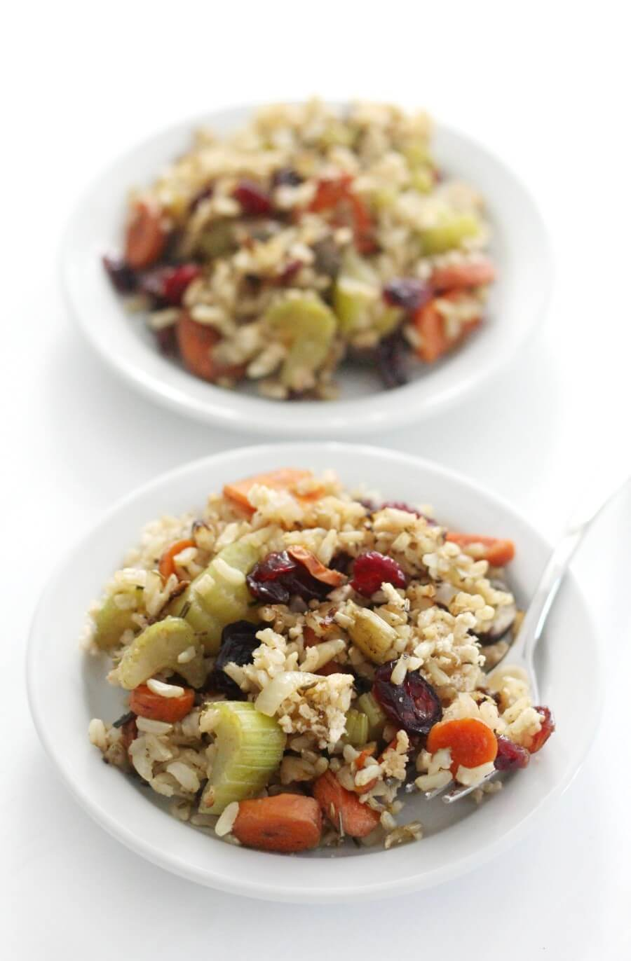 two white plates of gluten-free brown rice stuffing casserole