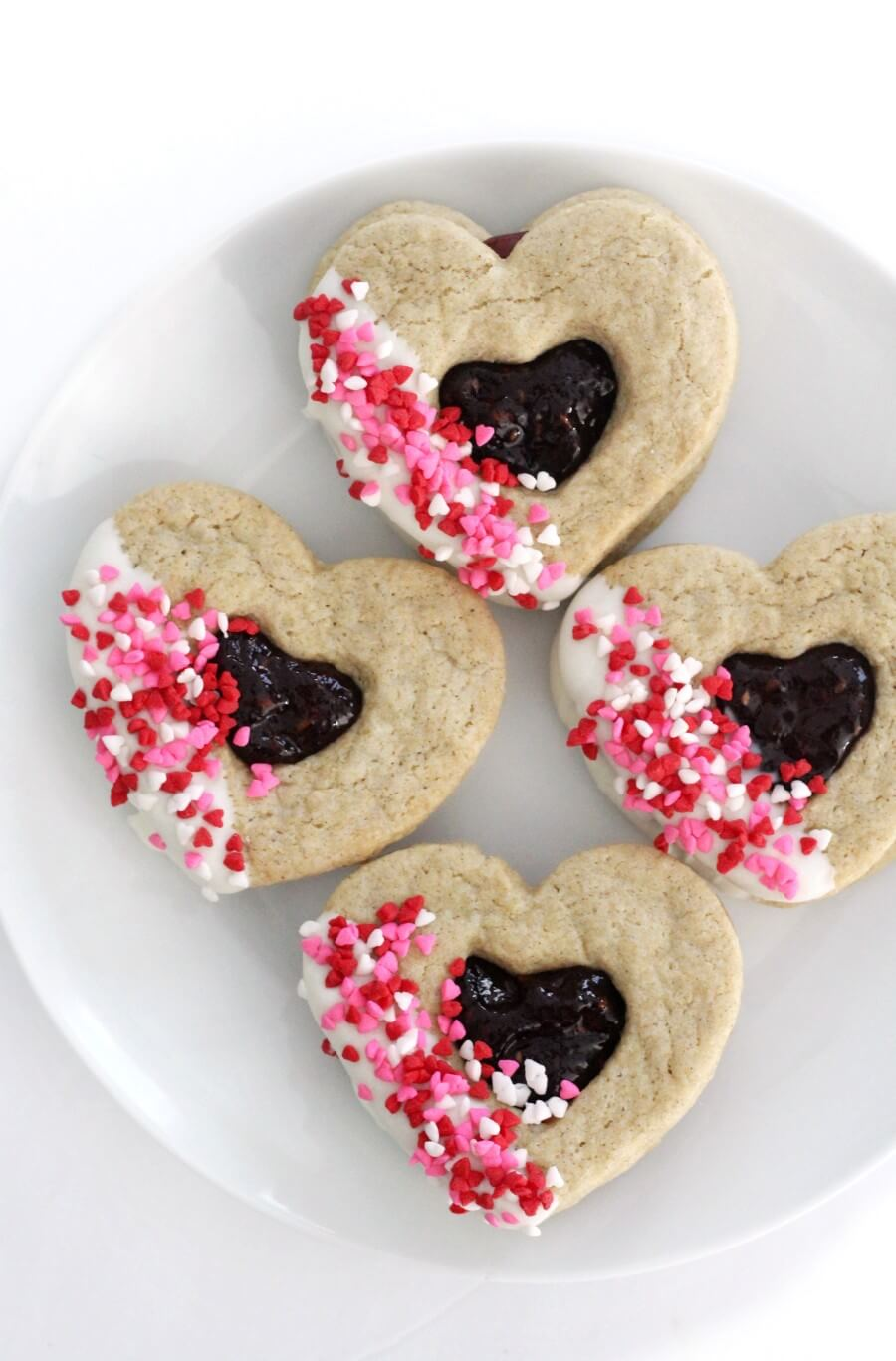 four heart-shaped valentine cookies on white plate