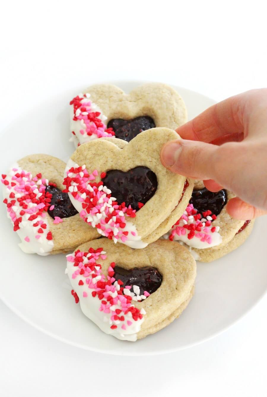 hand grabbing a gluten-free valentine's day heart cookie from plate