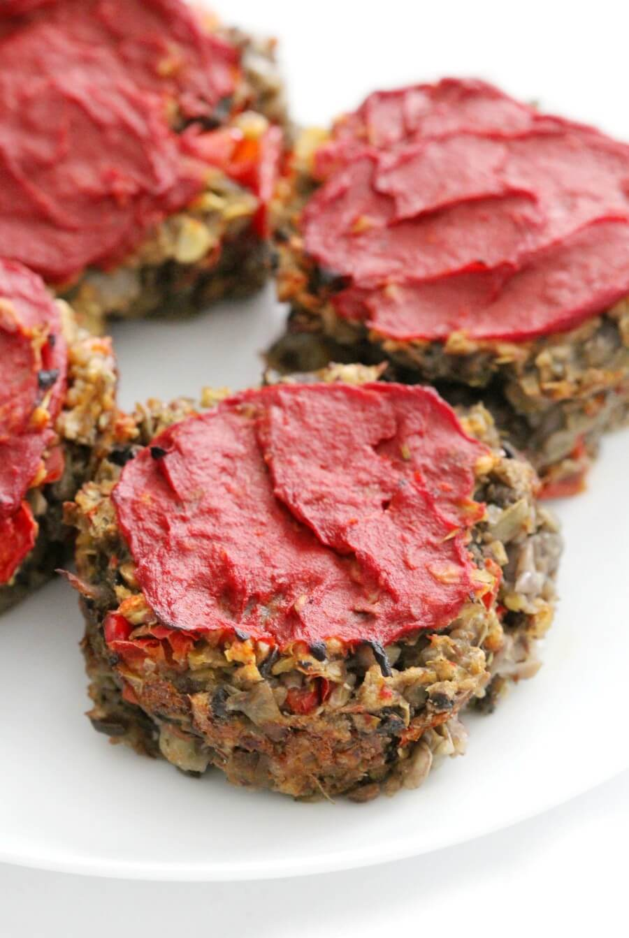 four mini vegan meatloaf muffins on white plate