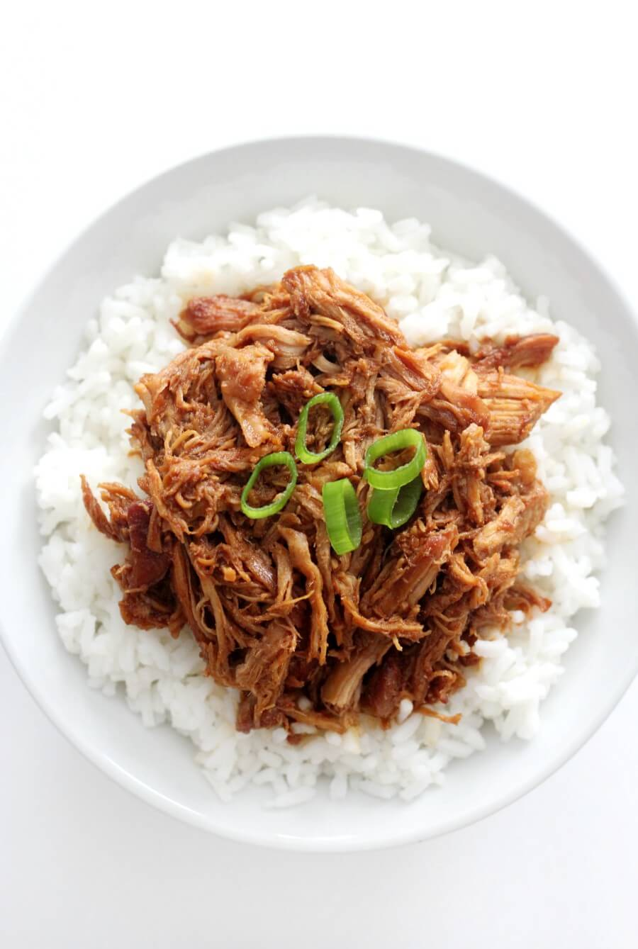 overhead centered view of shredded slow cooker honey garlic chicken on white rice