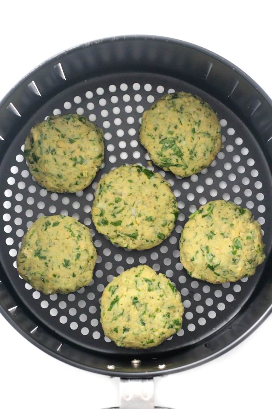 uncooked falafel patties in air fryer basket