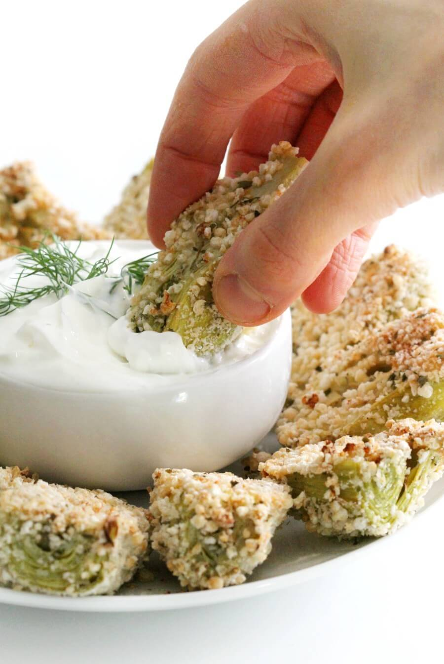 hand dipping a breaded artichoke heart in dairy-free yogurt dip