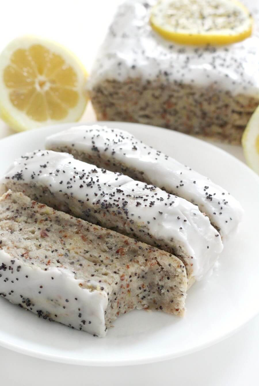whole loaf with slices and lemons of gluten-free lemon poppy seed bread