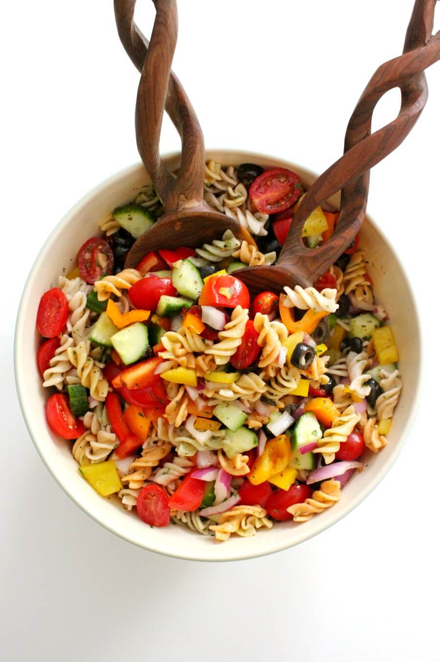 overhead view of gluten-free Italian pasta salad with wooden salad tongs