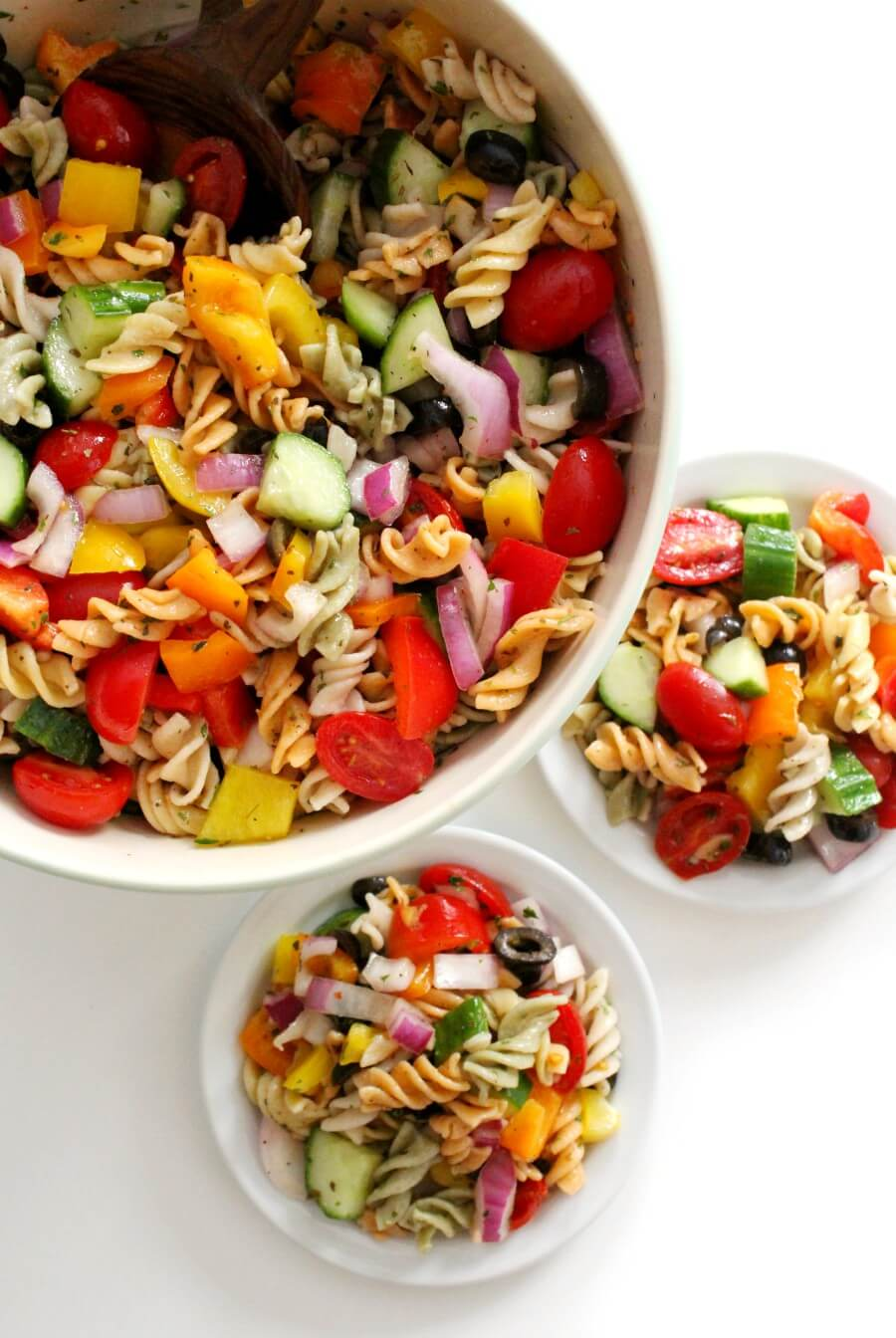 big bowl of classic Italian Pasta salad with two small serving plates
