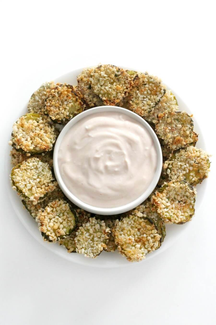centered overhead view of gluten-free air fryer fried pickles on plate with bowl of dip