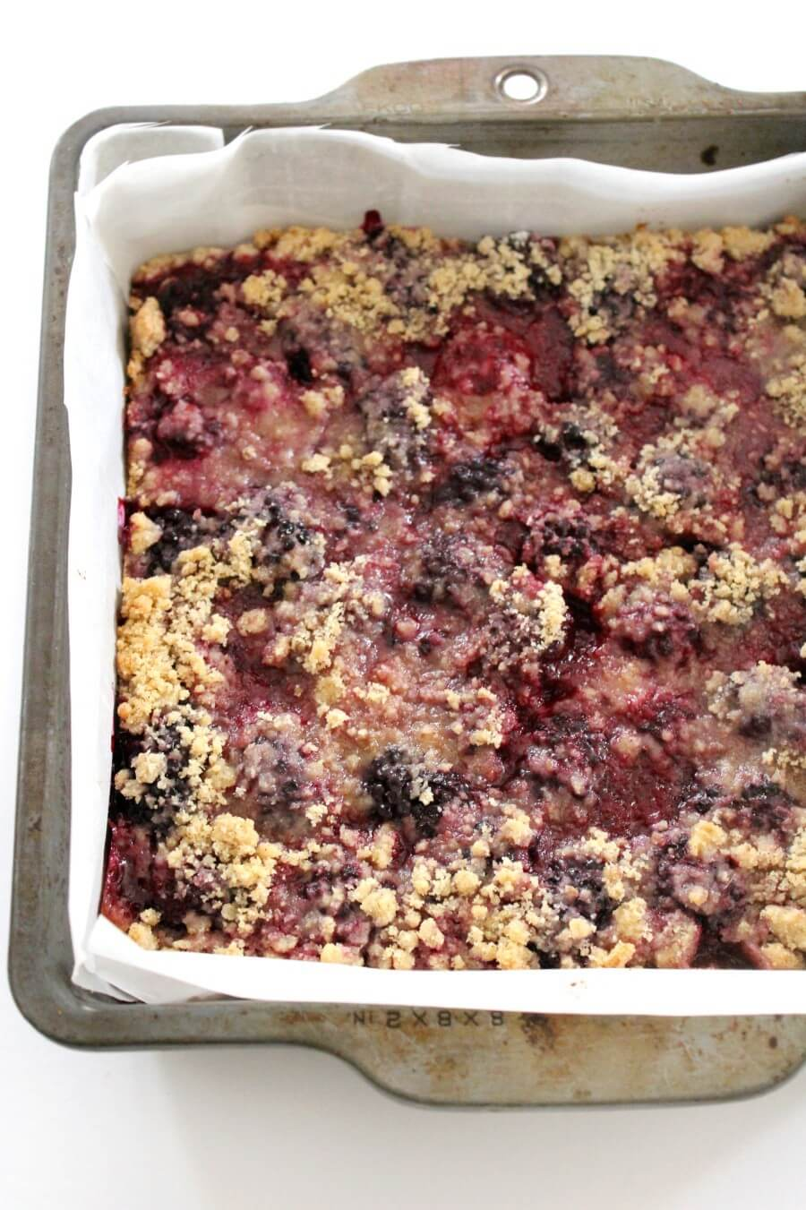 gluten-free blackberry crumb bars layered in baking pan with parchment paper