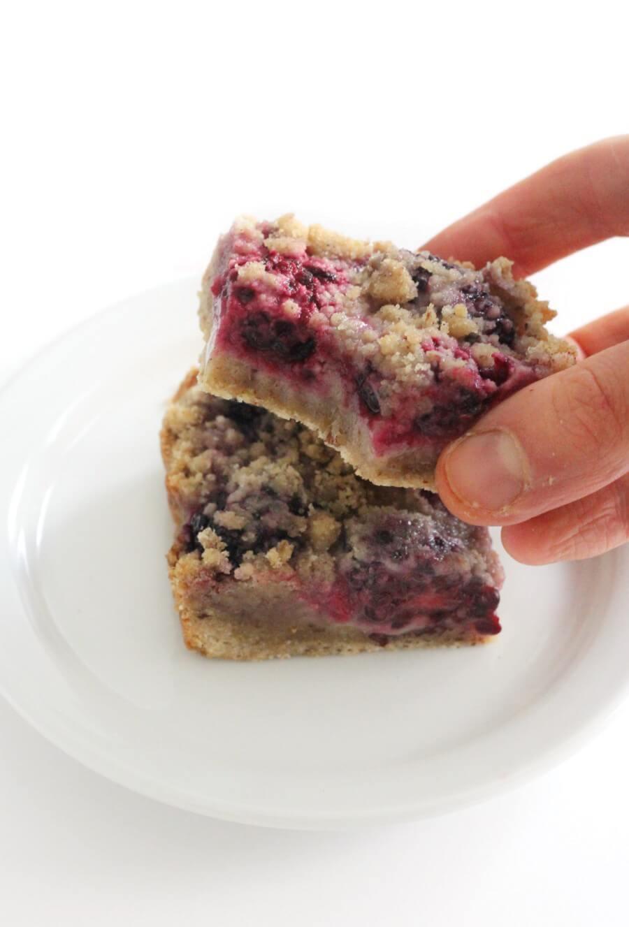 hand grabbing a bitten gluten-free blackberry crumb bar