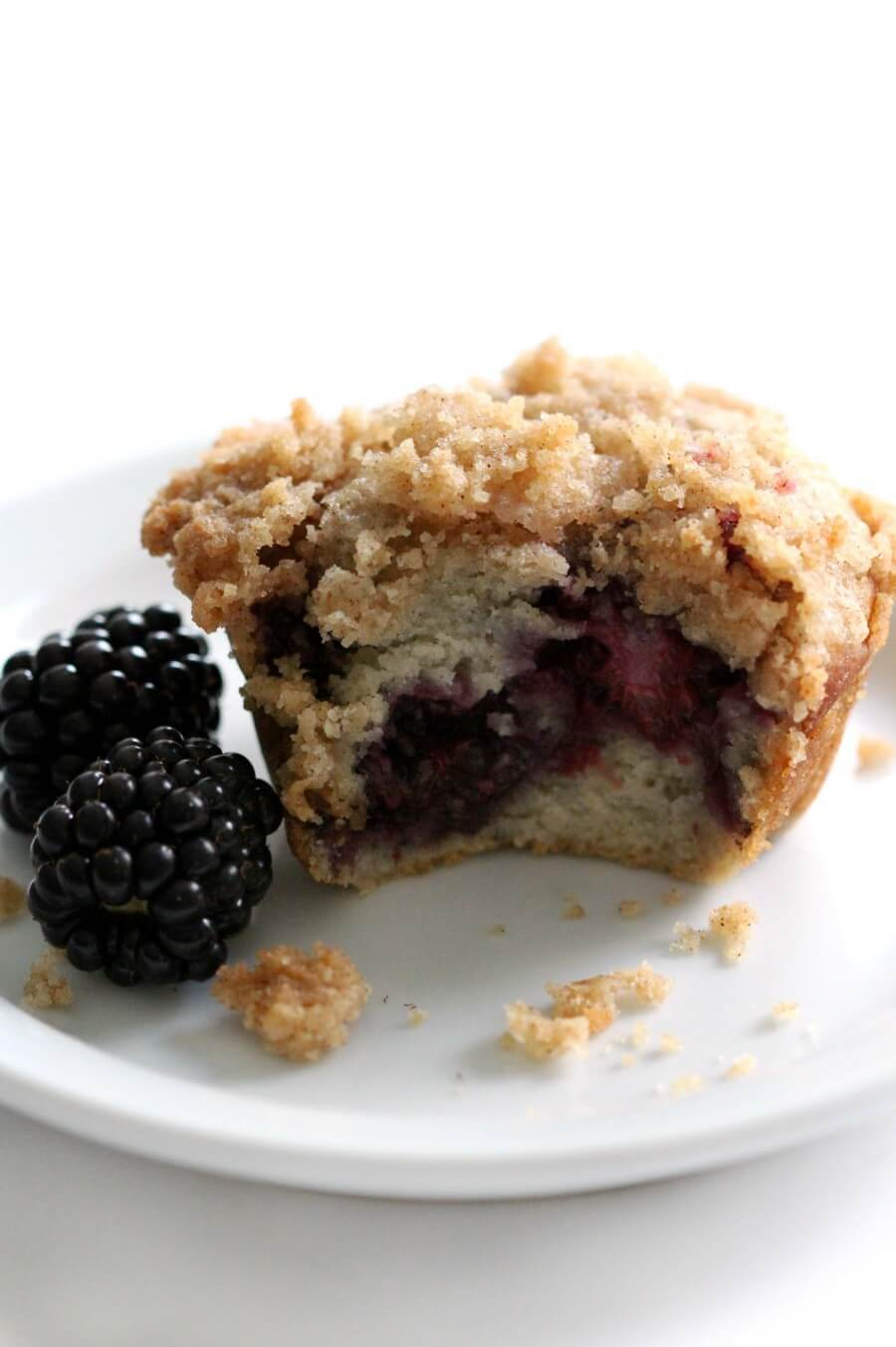bitten into gluten-free blackberry muffin on white plate with two blackberries