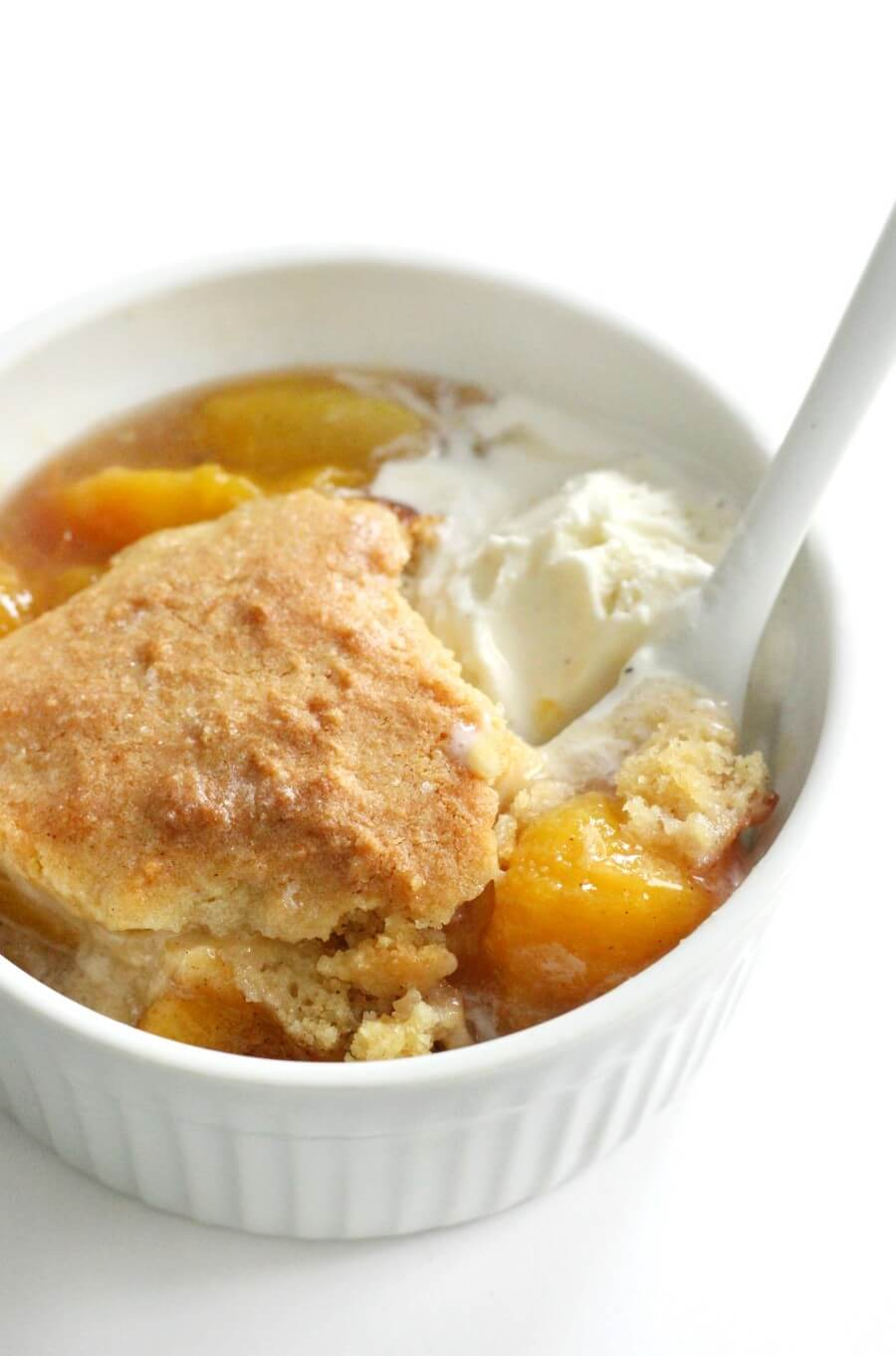 close-up of gluten-free peach cobbler in bowl with vegan ice cream