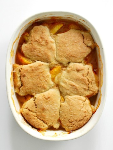 overhead view of finished gluten-free peach cobbler in white casserole dish