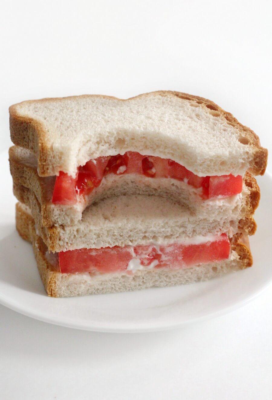 big bite taken out of a southern tomato sandwich
