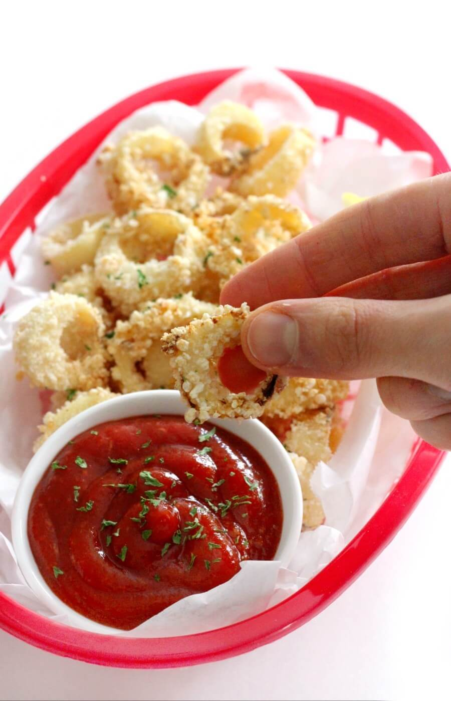 hand dipping a piece of vegan calamari in cocktail sauce