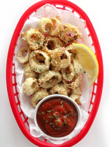 overhead view of vegan calamari with lemon and cocktail sauce in red basket