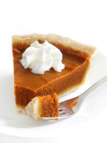 forkful and slice of gluten-free vegan pumpkin pie on plate with whipped cream