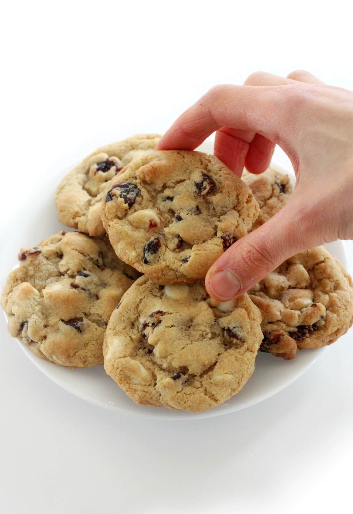hand grabbing a gluten-free white chocolate cranberry cookies from plate