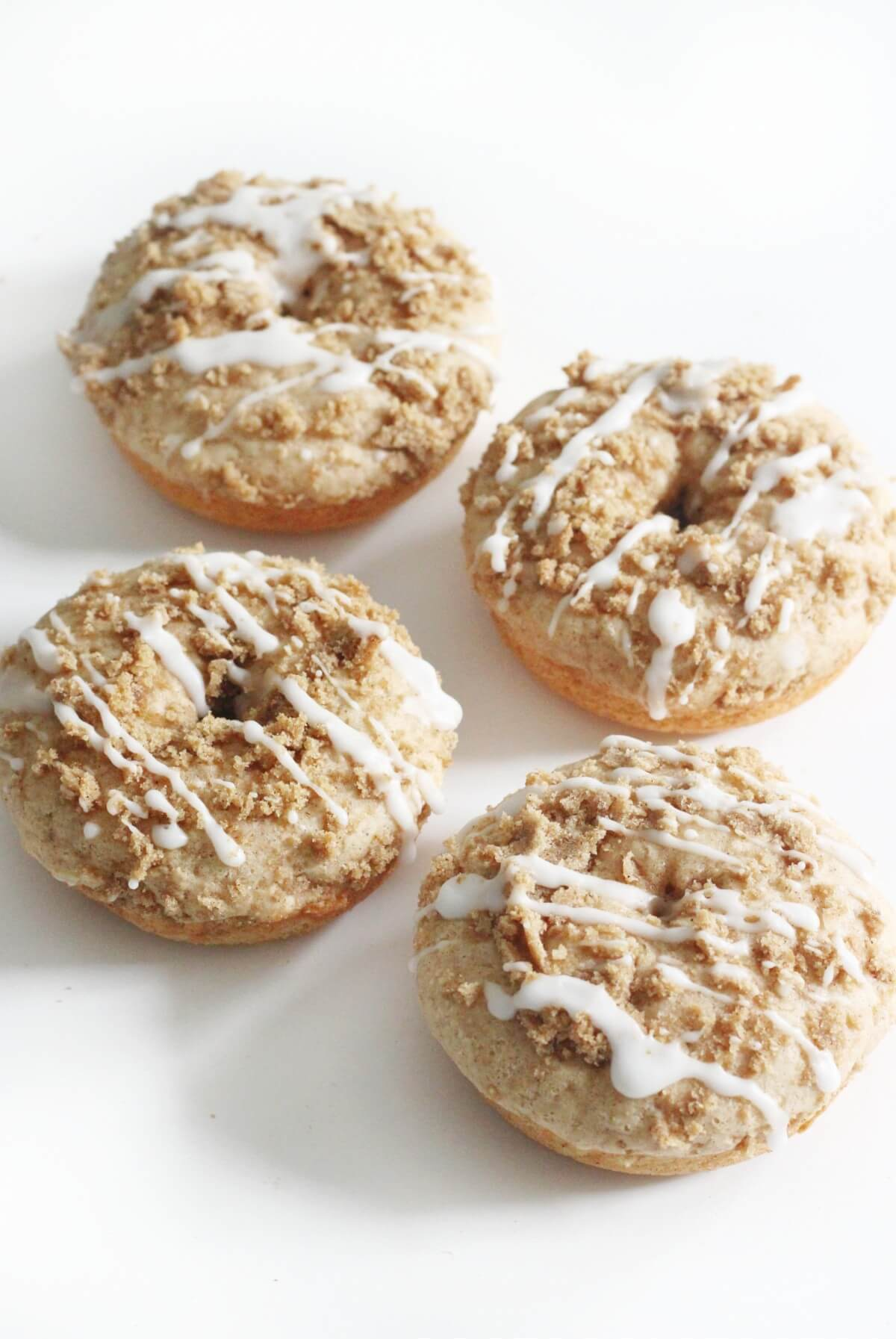 four gluten-free coffee cake doughnuts on white table