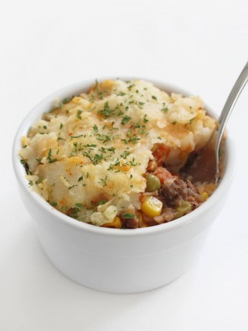 single white ramekin with vegan lentil shepherd's pie being eaten