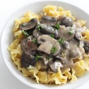 vegan mushroom stroganoff over gluten-free noodles in white bowl