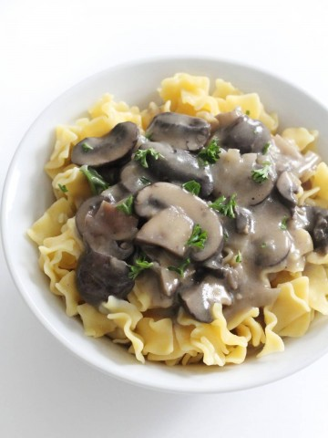 vegan mushroom stroganoff over gluten-free noodles in white bowl