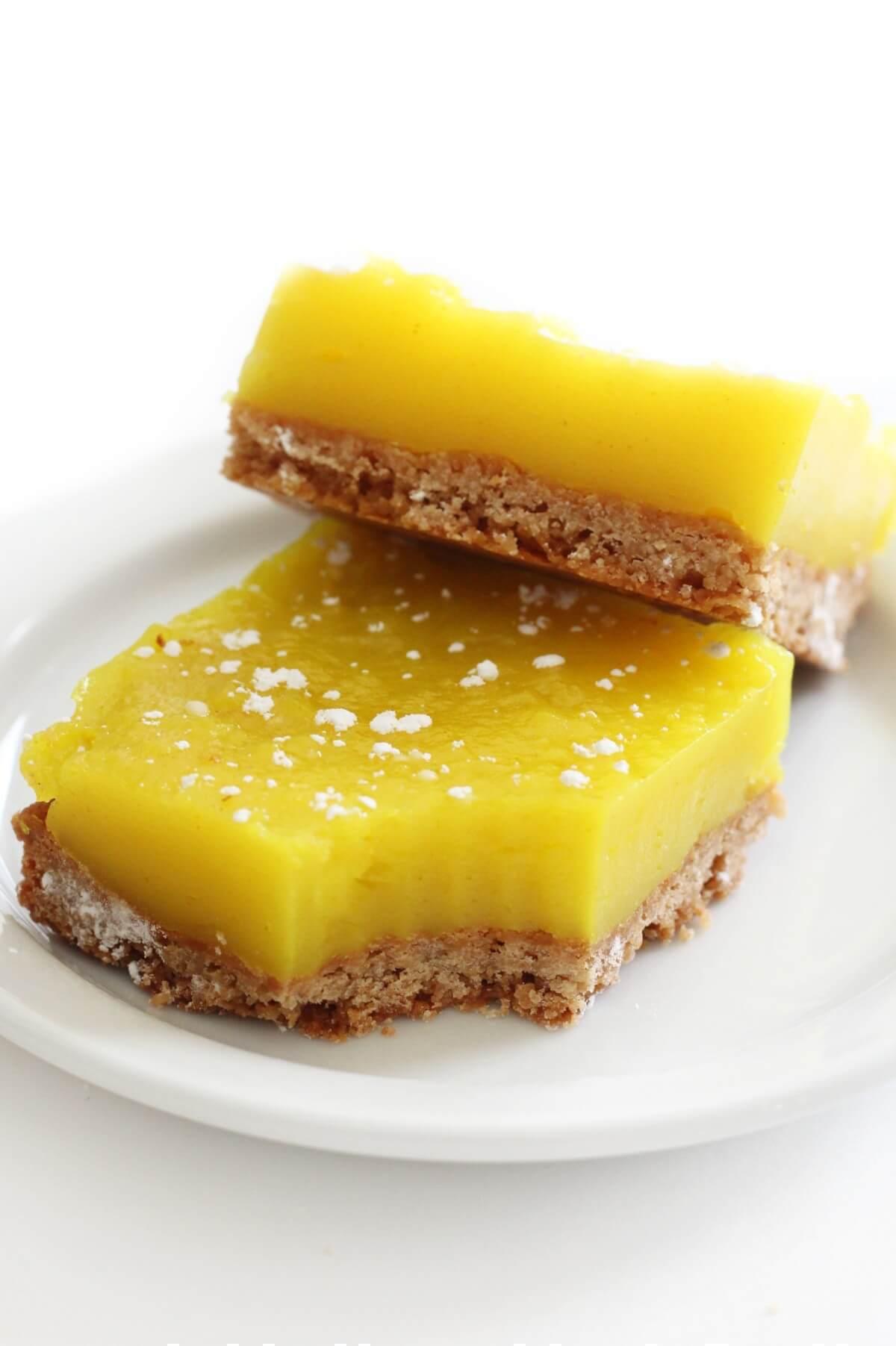 two vegan lemon bars on a white plate