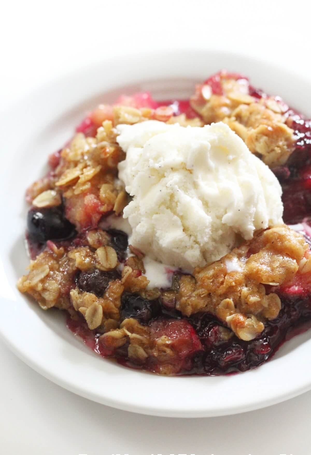 close up of gluten-free blueberry rhubarb crisp with vegan ice cream