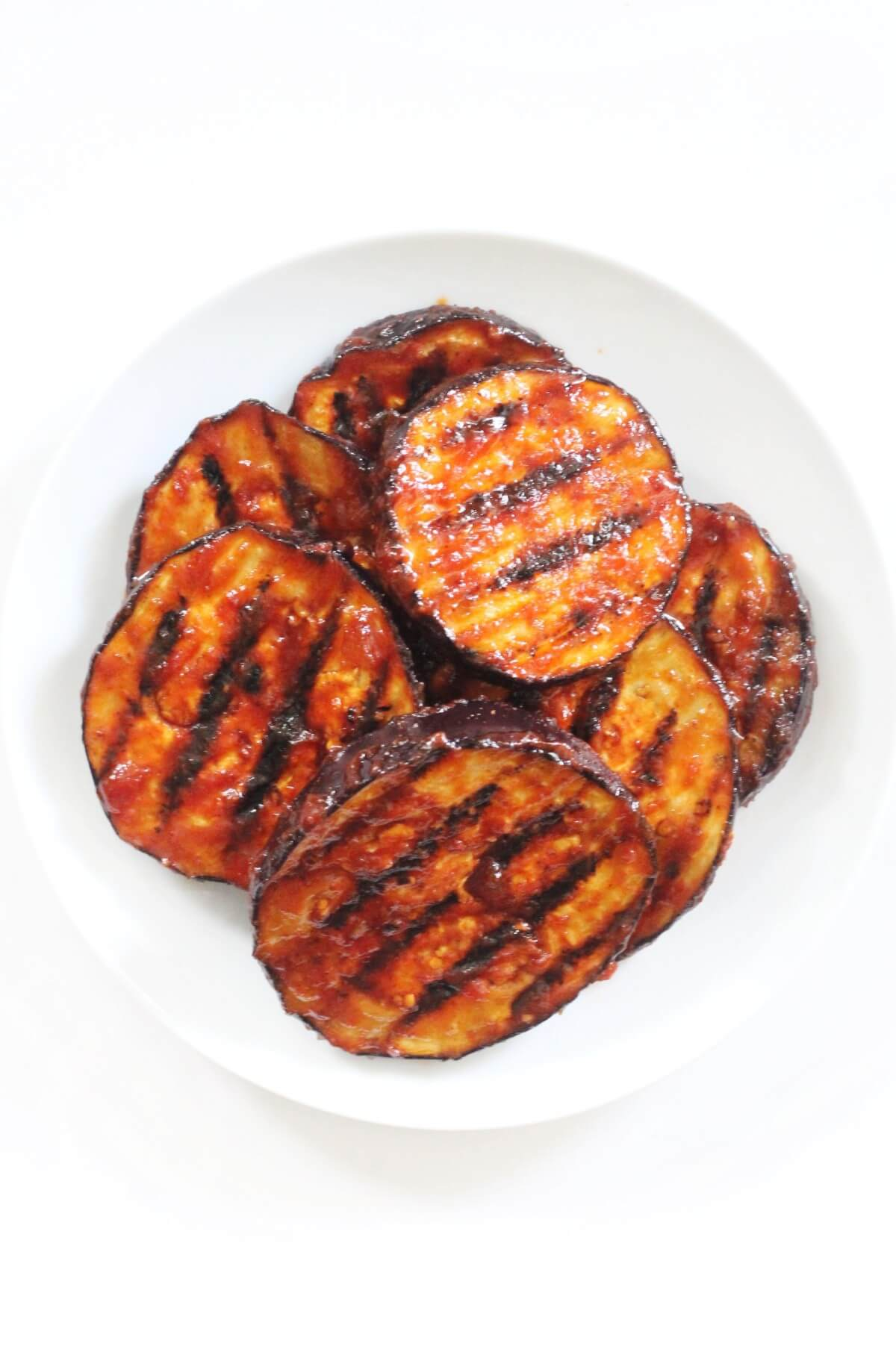 centered overhead view of plate of bbq grilled eggplant slices